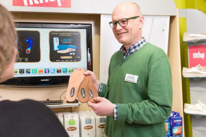 Geschäftsführer Bernd Borgmann berät über Schuheinlagen in Foot Solutions Laden