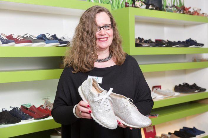 Frau zeigt zwei Modelle von Markenschuhen im Foot Solutions Fachgeschäft in die Kamera