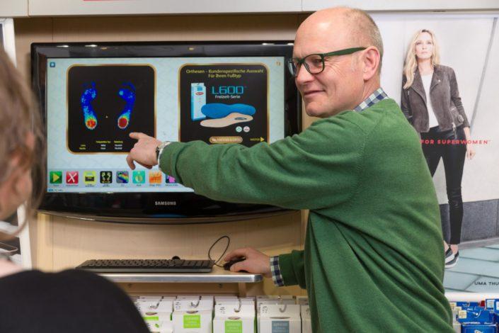 Geschäftsführer Bernd Borgmann zeigt auf dem Bildschirm die Ergebnisse von der digitale Fußmessung an eine Kundin