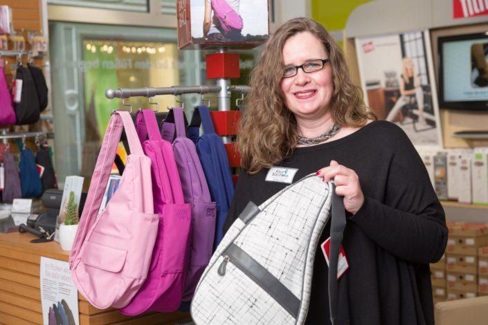 Frau hält eine graue Rückentasche neben dem Ständer mit Health Back Bag Taschen im Fachgeschäft