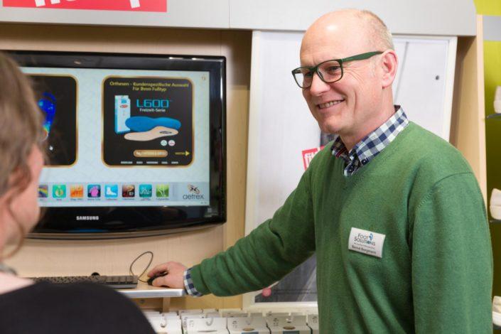 Geschäftsführer Bernd Borgmann gibt einer Frau professionelle Beratung über die passenden Einlagenmodelle und dabei werden die Bilder auf dem Computer gezeigt