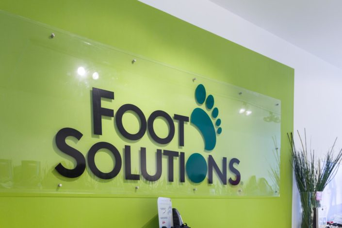 Glasschild mit Foot Solutions Logo in der Filiale