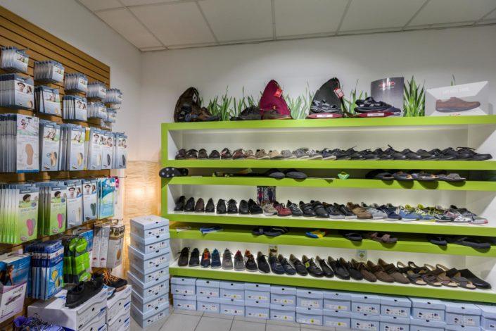 Abbildung von den Regalen mit bequemen Markenschuhen und Schuheinlagen in Foot Solutions Filiale