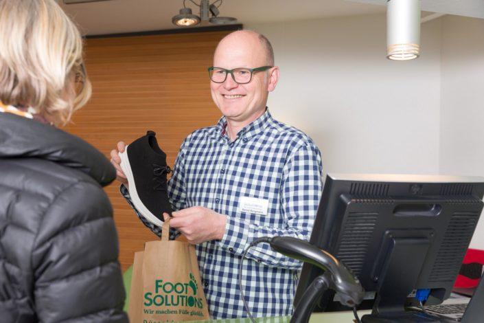 Geschäftsführer Bernd Borgmann packt die gekauften schwarzen Aktivschuhe in die Papiertüte von Foot Solutions