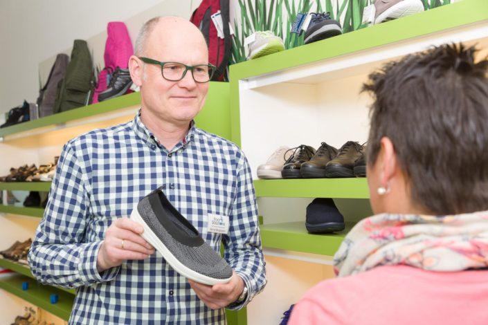 Geschäftsführer Bernd Borgmann hält Schuh zum Verkauf an eine Kundin in der Hand