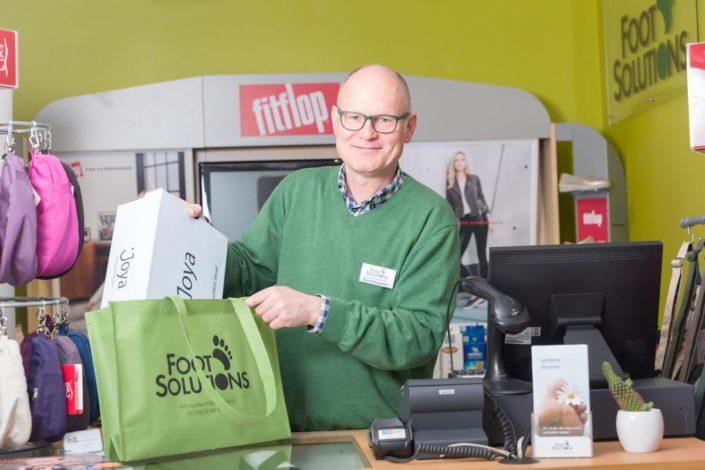 Geschäftsführer Bernd Borgmann packt den Schuhkarton mit gekauften Schuhen der Marke Joya in die Tasche an der Kasse