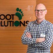 Geschäftsführer Bernd Borgmann vor dem Glasschild mit dem Foot Solutions Logo drauf