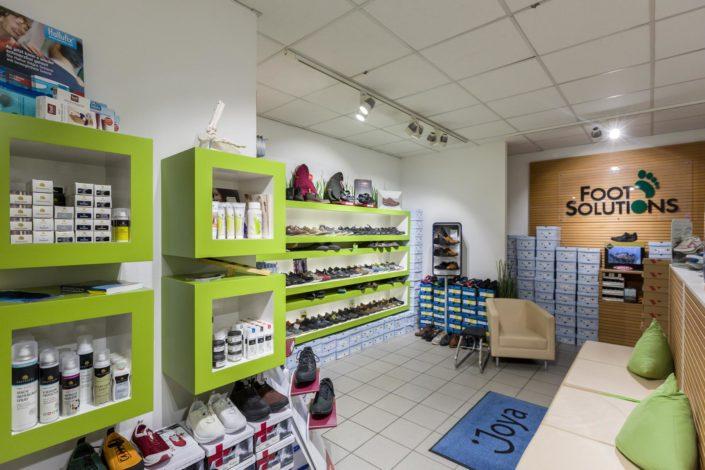 Abbildung von den Regalen mit Imprägnierspray und anderen Fuß Accessoires in Foot Solutions Filiale