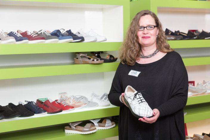 Frau steht vor dem Schuhregal und hält ein Modelle von Komfortschuhen in die Kamera